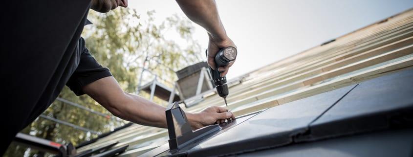 Ein meindach Dachdecker, der an einem Dach arbeitet