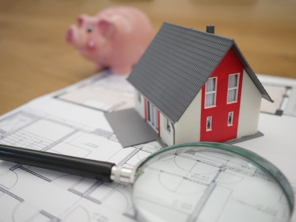 Ein Sparschwein, ein Modell eines Hauses mit neuem Dach