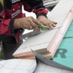 ein Dachdecker, der mit Dämmstoffe arbeitet