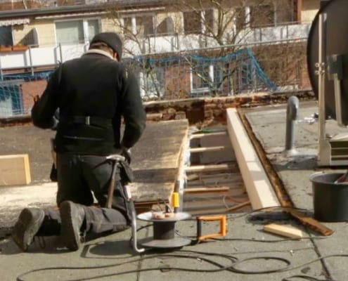 Dachdecker arbeiten an einem Schimmel befallen Flachdachleck