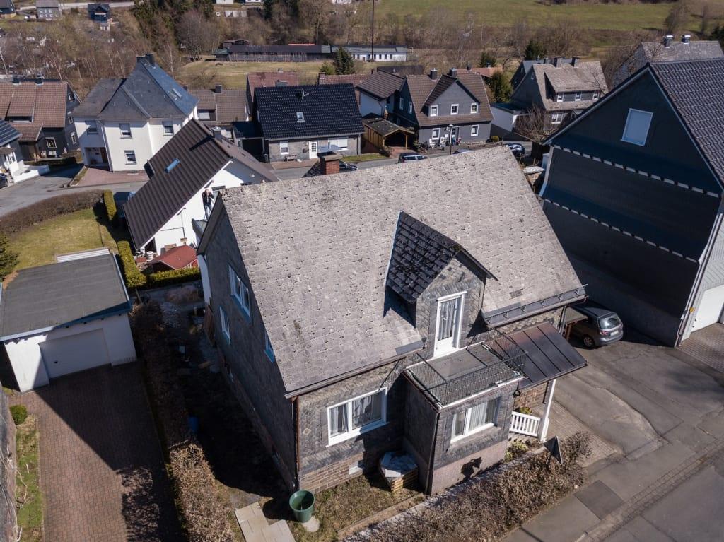 Ein Haus mit Asbestdach vor der Renovierung mit einem leichten Dach