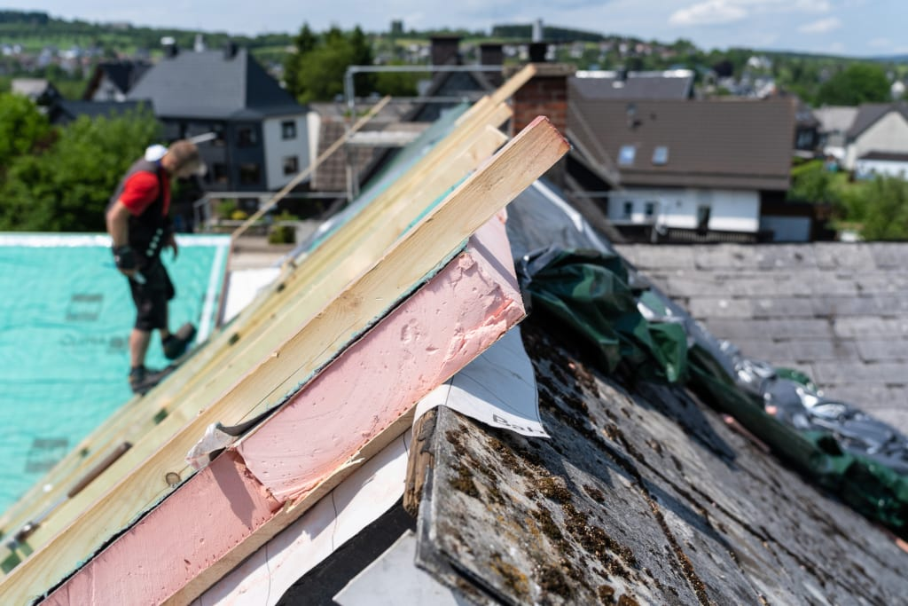 Ein Haus mit Asbestbrettern wird mit einem leichten Dach renoviert