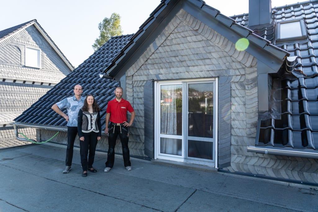 Hausbesitzer stehen nach erfolgreicher Dachsanierung beim Dachdecker