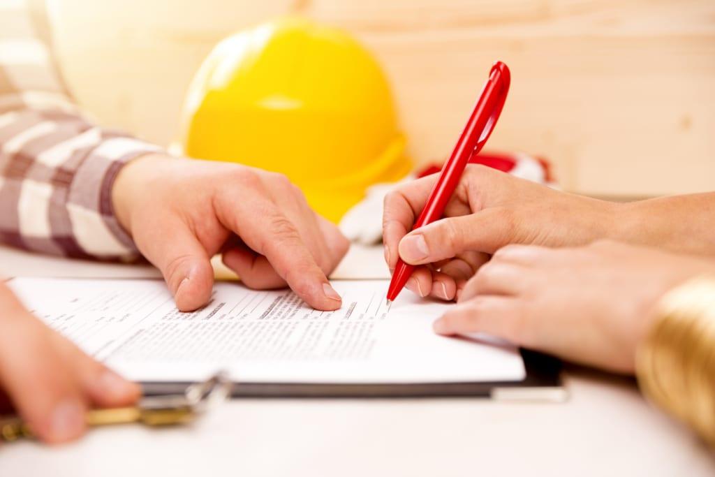 Ein Hausbesitzer unterzeichnet einen Vertrag mit einer Dachdeckerfirma