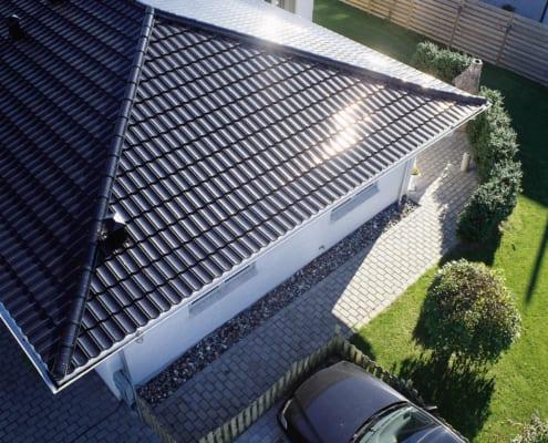 Ein neues haus mit einem Auto, das draußen geparkt ist, für Leute, die sich viel fragen, Was kostet ein neues Dach