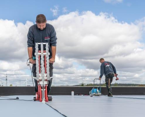 Professionelle Dachdecker arbeiten auf einem Flachdach