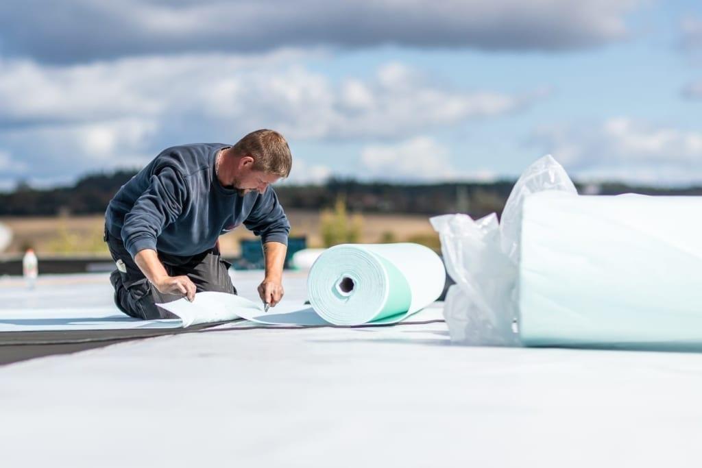 Dachdecker bei der Arbeit an der Dachsanierung gewerblicher Gebäude