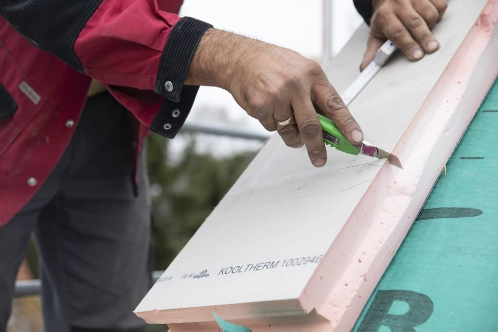 ein Dachdecker, der dank des Klimapakets an der Dachisolierung arbeitet