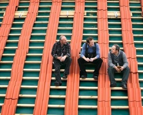 Eine Gruppe deutscher Dachdecker sitzt auf einem Ziegeldach
