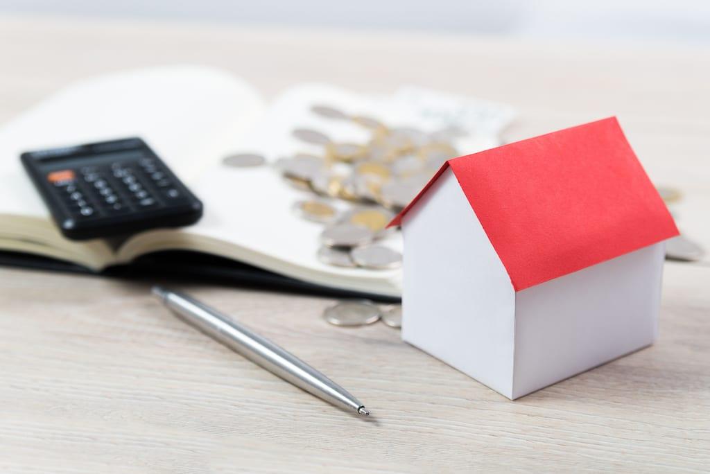 Ein Musterhaus mit einem roten Dach, einem Taschenrechner, der das Scheunendach finanziert
