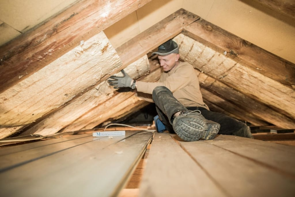 Ein Meindach-Dachdecker installiert die Dachisolierung, die Teil des Klimapakets ist