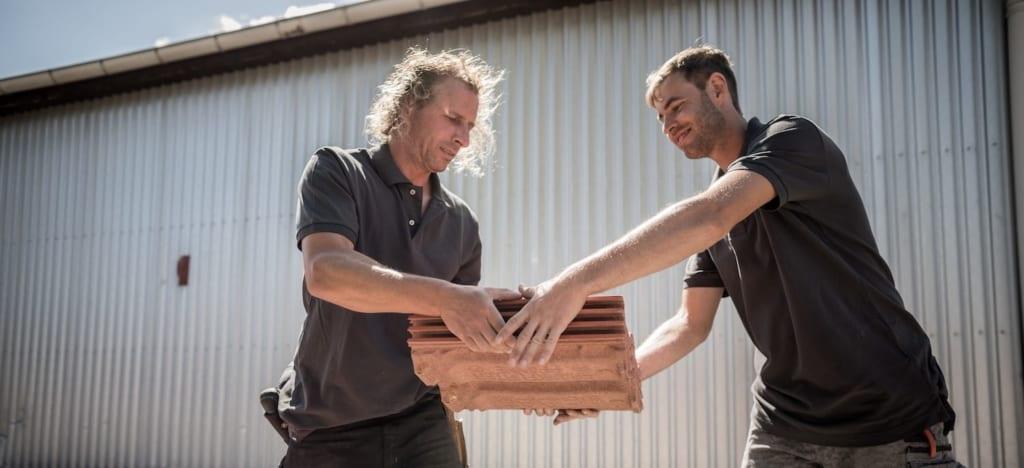 Die Dachdecker von meindach verarbeiten Materialien für die Reparatur von Scheunendächern