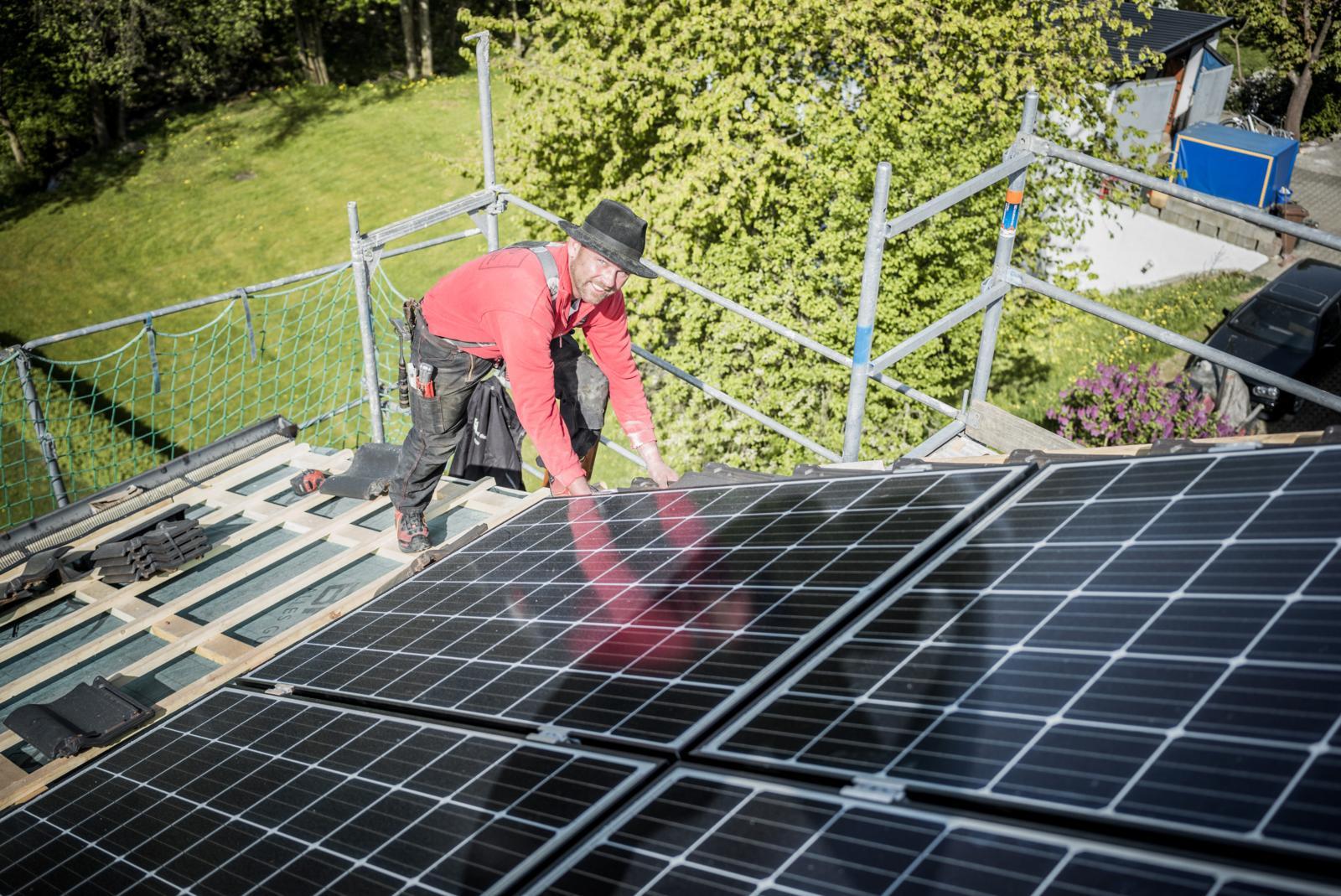 Ein Meindach-Dachdecker installiert Sonnenkollektoren, die Teil des Klimapakets sind
