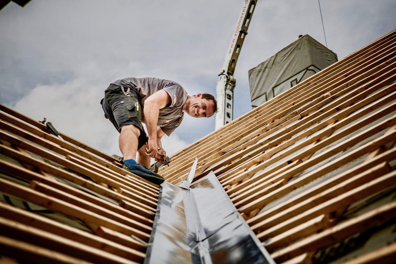 Ein MeinDach-Dachdecker arbeitet an einer Dachsanierung
