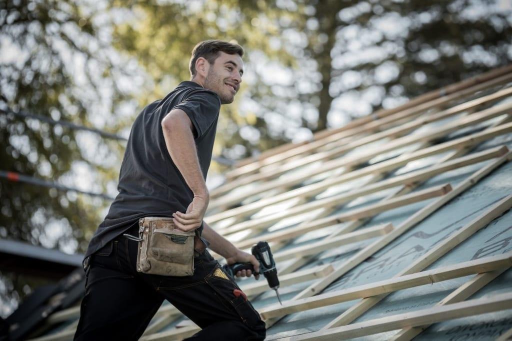 Ein Meindach-Dachdecker, der auf einem Schrägdach arbeitet