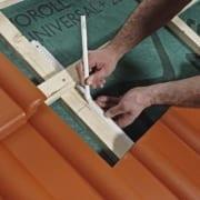 Ein Dachdecker führt eine Berechnung durch