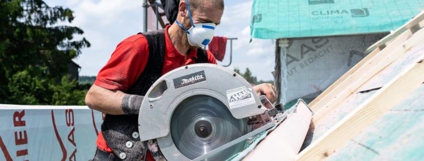 Ein professioneller Dachdecker, der Zimmerarbeiten auf einem Dach erledigt