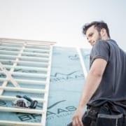 Ein Dachdecker, der in Deutschland auf einem Dach arbeitet