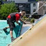 ein Dachdecker, der an einem neuen Dach arbeitet