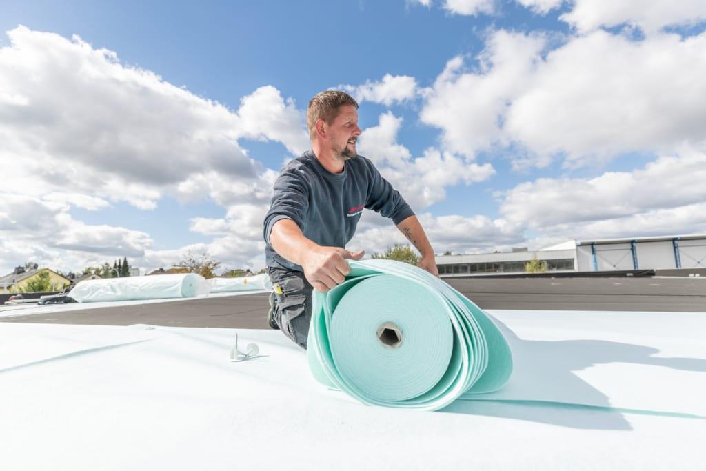 Ein professioneller Dachdecker von meindach installiert ein Flachdach auf einem Geschäftsgebäude