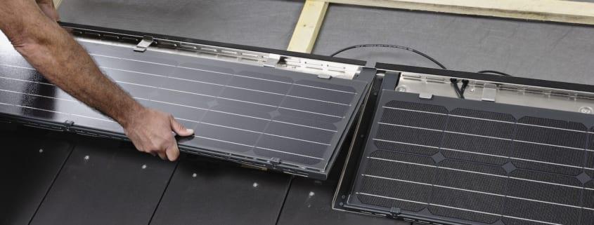 Ein Dachdecker installiert eine Solaranlage auf dem Dach