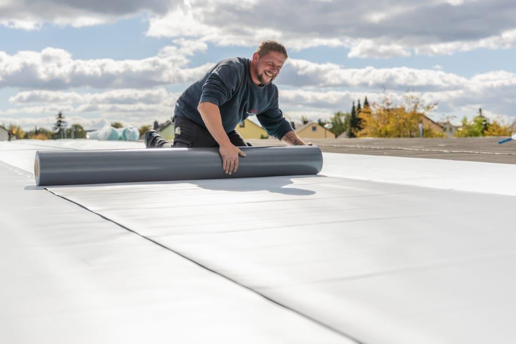 Ein Dachdecker, der auf einem kommerziellen Flachdach arbeitet