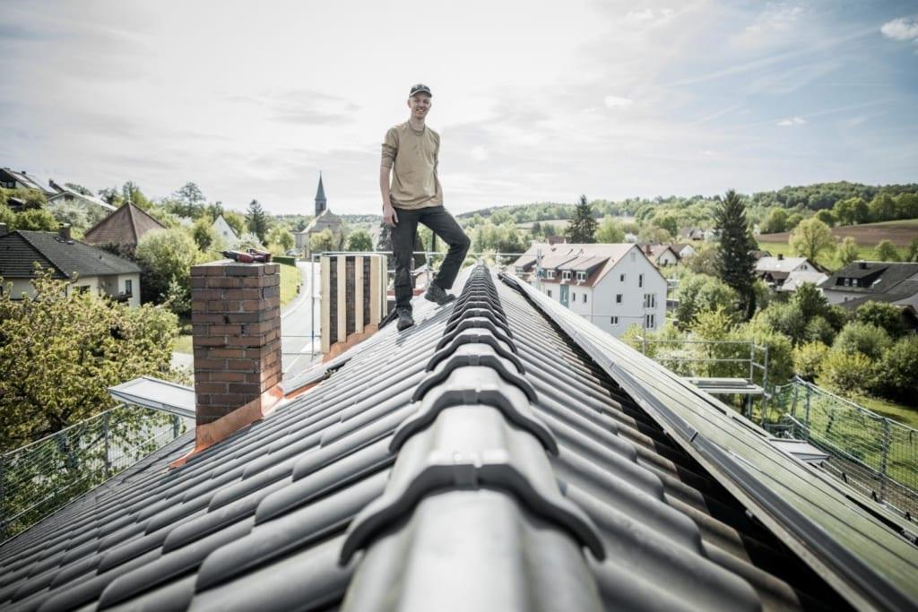 Ein professioneller Dachdecker, der auf einem geneigten Dach steht