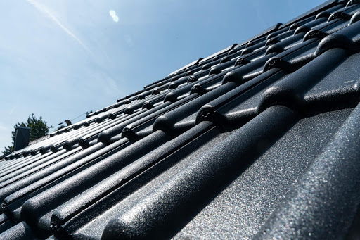 Schwarze Dachziegel auf einem Schrägdach an einem sonnigen Tag