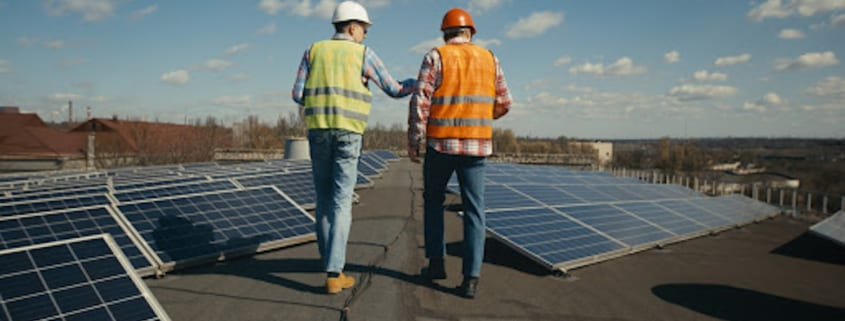 Professionelle Dachdecker untersuchen ein Industriedach auf Problem auf Beschädigungen