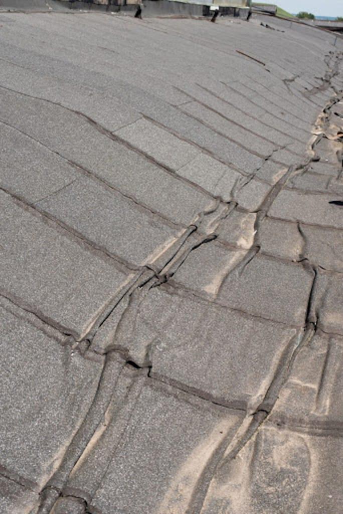 Ein altes kommerzielles Flachdach, mit Beschädigte Isolationsschicht, das renoviert oder ersetzt werden muss
