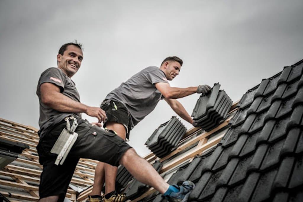 Professionelle Dachdecker arbeiten an einer modernen Dachform