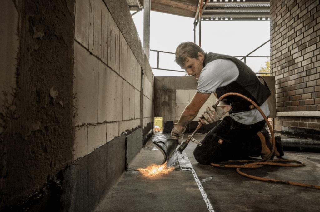 Deutscher Dachdecker, der auf einem Industriedach arbeitet