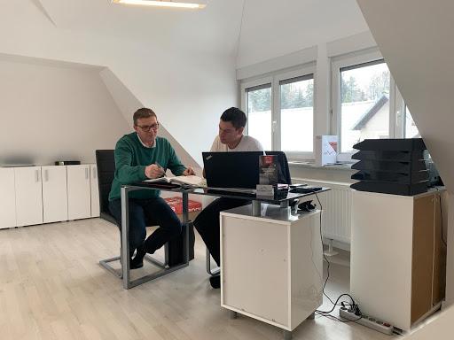 Hausbesitzer und Dachdecker besprechen die Dachrenovierung