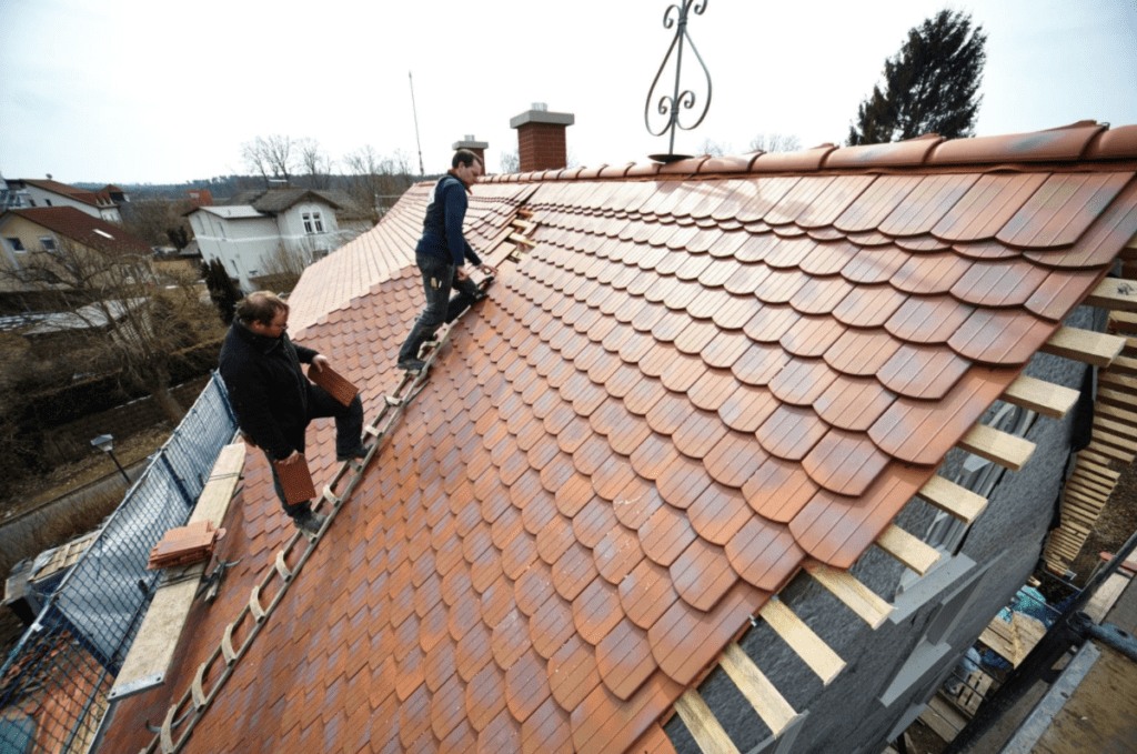 Dachdecker arbeiten auf einem Ziegeldach in Deutschland
