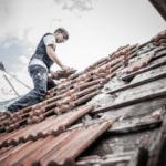 Ein professioneller Dachdecker, der sicher (mit sozialer Distanz) auf einem alten Dach arbeitet