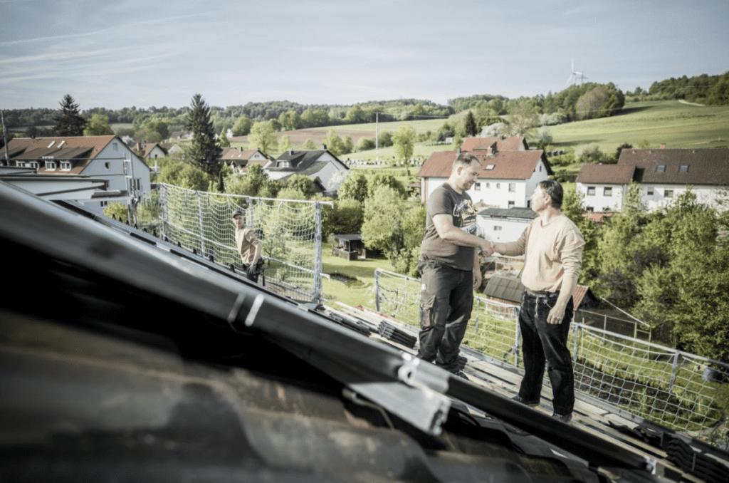 2 MeinDach-Dachdecker arbeiten auf einem Dach