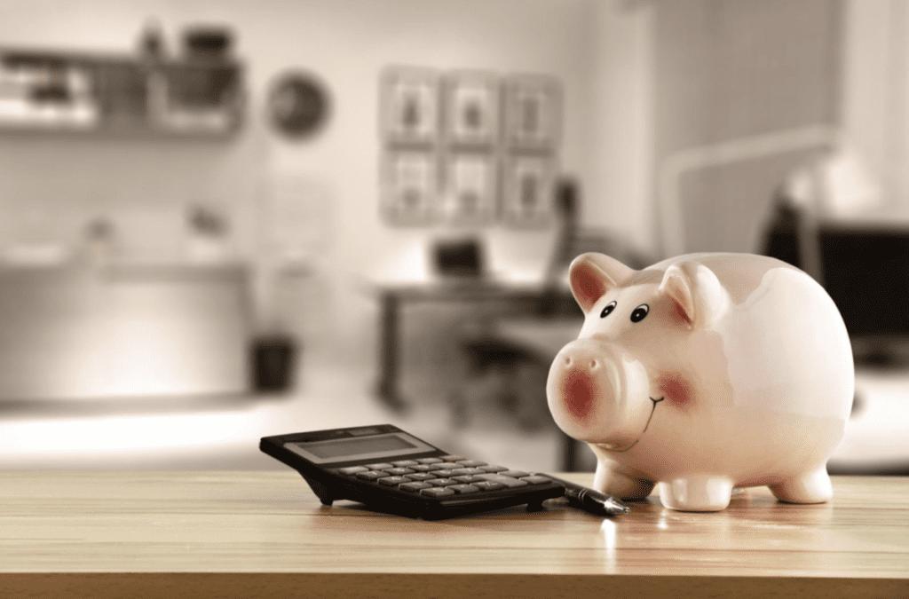 Eine Sparkasse und ein Taschenrechner symbolisieren die Kosteneffizienz bei der Planung einer Dachrenovierung