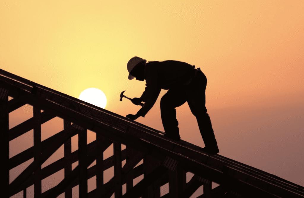 Dachdecker arbeiten an Sparren aus Holz, Sonnenuntergang